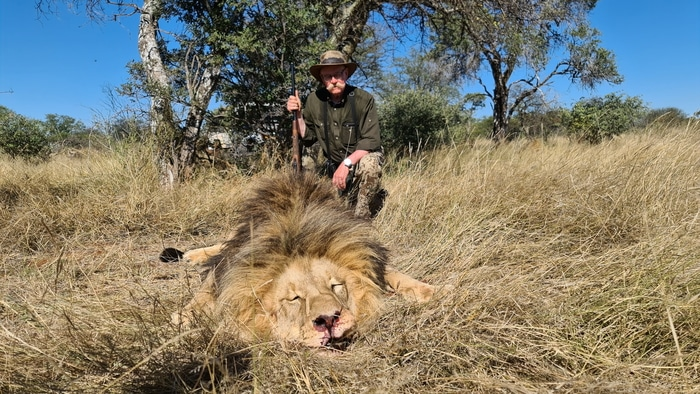 Hunter with his lion trophy after the hunt